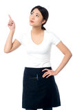 Asian waitress pointing and looking away Stock Photography