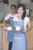 Asian waitress serving coffee Stock Photo