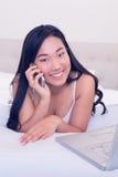 Asian waitress smiling at camera lying on bed talking on phone Stock Photos