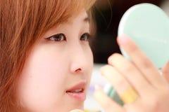 Asian waman making up her face Stock Photography