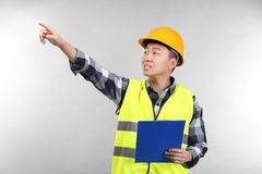 Asian warehouse worker with clipboard pointing. At something, on light background Royalty Free Stock Image