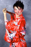 Asian Warrior. A man in a Geisha outfit, holding a sword Stock Photography