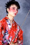 Asian Warrior. A man in a Geisha outfit, holding a sword stock images