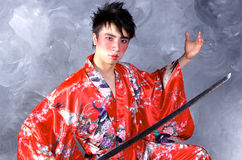 Asian Warrior. A man in a Geisha outfit, holding a sword royalty free stock photography