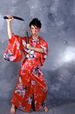 Asian Warrior. A man in a Geisha outfit, holding a set of Nunchaku in a fighting stance Stock Image