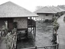 Asian water village. Asian huts or houses built on stilts over water and connected by wooden walkways royalty free stock photo