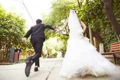 Asian newly-wed running on street Royalty Free Stock Photography