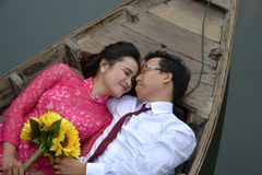Asian wedding couple on wooden boat
