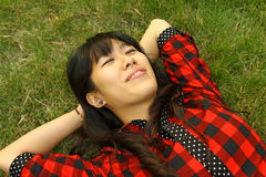 An Asian who is sleeping on the grass. She is very relax with smiling face Stock Images