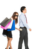 Asian Wife Stealing Money Husband Pocket Walking. A shopaholic, greedy Asian wife with sunglasses, department store bags, steals money unnoticed from the pants Royalty Free Stock Image