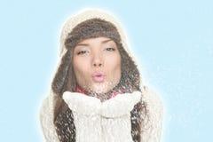 Asian winter woman blowing snow kiss. Christmas winter woman blowing snow kiss. Isolated on blue background. Asian woman Royalty Free Stock Image