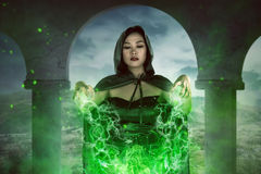 Asian witch woman spelling with concentration. Asian witch woman casting spell with concentration, the green light out from her hand stock photo