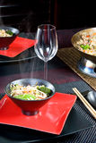 Asian wok. Restaurant table setting with oriental wok food or stir-fry Royalty Free Stock Photo