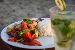 Asian wok and cocktail. Asian cuisine made of mixed vegetable and chicken wok with rice along with a mojito cocktail Stock Images