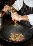 Asian Wok Cooking. Chef adds ground pepper to vegetable and meat foods cooking in wok Royalty Free Stock Photos