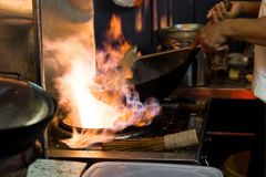 Asian wok cooking  with flames in an open style street food kitc Stock Photography