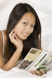 Asian woman. In early 20's laying in bed reading magazine Stock Photography