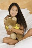 Asian woman. In early 20's sitting in bed hugging a teddy bear Stock Photos