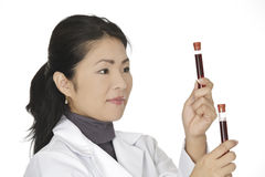 Asian woman laboratory technician examining a tube of blood  Stock Photo