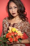 Asian woman. Portrait of a woman with roses. Asian. The background is red Stock Photos