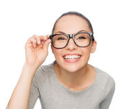 Asian woman in adjusting eyeglasses. Happiness, health and vision concept - smiling asian woman adjusting eyeglasses stock photo