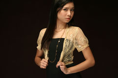 Asian woman against a dark background. Asian girl in black dress against dark background royalty free stock photos