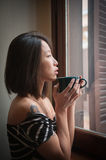 Asian woman alone with green cup between hands Stock Photos