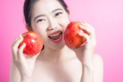 Asian woman with apple concept. She smiling and holding apple. Beauty face and natural makeup. Isolated over pink background. Royalty Free Stock Images