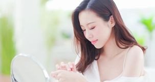 Asian woman applying hand cream royalty free stock image