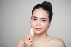Asian woman applying hygienic lip balm over grey background.  stock image