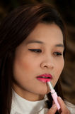 Asian woman applying make up. Royalty Free Stock Photography