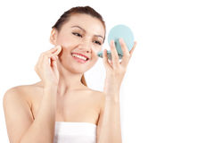 Asian woman applying makeup and smiling Royalty Free Stock Image