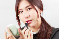 Asian woman applying makeup, using lipstick, for beauty concept royalty free stock photography