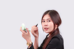Asian woman applying makeup, using lipstick, for beauty . Royalty Free Stock Image