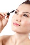 Asian woman applying mascara. Beautiful asian woman applying mascara and smile, isolated on white Royalty Free Stock Image