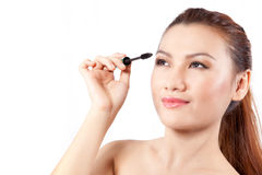 Asian woman applying mascara with copy space Royalty Free Stock Photos