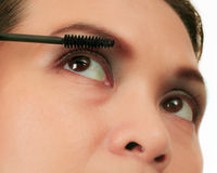 Asian woman applying mascara on white. Stock Image