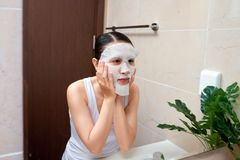 Asian woman applying mask on her face and looking in the mirror stock photos
