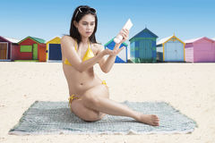 Asian woman applying sunscreen near the cottage Stock Photography