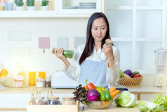 Asian woman in an apron cooking healthy food stock photos