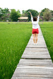Asian woman arms up on wood walk  way Stock Image