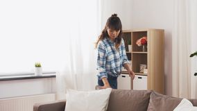 Asian woman arranging sofa cushions at home stock footage