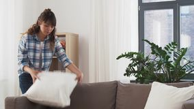 Asian woman arranging sofa cushions at home stock video footage