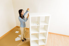 Asian woman assemble a white bookshelf Stock Images