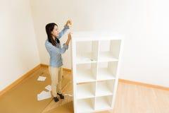 Asian woman assemble a white bookshelf Stock Images