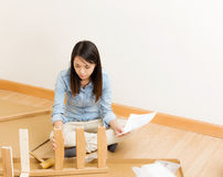 Asian woman assembling chair by hammer with instruction Stock Photos