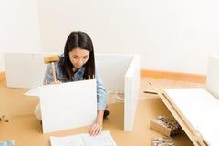 Asian woman assembling closet Royalty Free Stock Image
