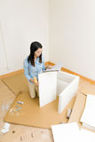 Asian woman assembling closet with instruction Royalty Free Stock Image