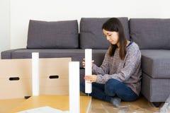 Asian woman assembling new furniture Royalty Free Stock Image