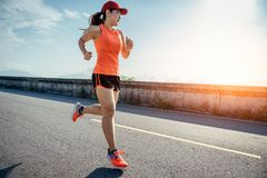 An asian woman athletic is jogging on the concrete road stock photos